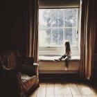 Маленькая девочка, выглядывающая из окна — стоковое фото