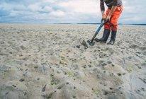 Ragazzo scavare per clamming sulla spiaggia — Foto stock