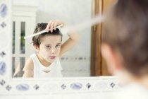 Мальчик расчесывает волосы — стоковое фото
