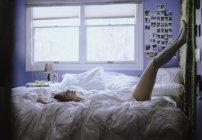Молода жінка, лежачи на ліжку — стокове фото