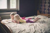 Две девушки лежат на кровати — стоковое фото