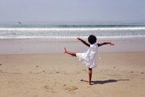 Ragazza in piedi su una gamba sulla spiaggia — Foto stock