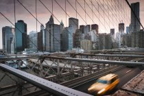 Yellow cab driving across Brooklyn Bridge — Stock Photo