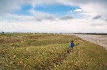 Boy running through grass — Stock Photo
