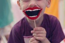 Menino segurando sorriso adereço no pau — Fotografia de Stock