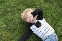 Boy lying on ground — Stock Photo