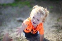 Улыбающийся мальчик на четвереньках — стоковое фото