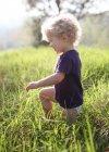 Хлопчик на колінах в траві — стокове фото