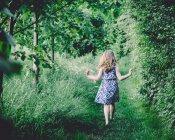 Девушка, идущая через лес — стоковое фото