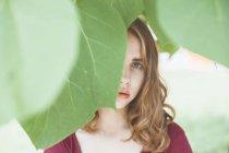 Donna con il viso nascosto da foglie — Foto stock