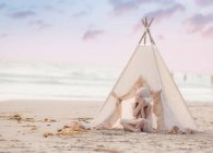 Girl sitting in wigwam on beach — Stock Photo