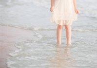 Jeune fille debout en surf sur la plage — Photo de stock