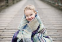 Boy wrapped in blanket — Stock Photo