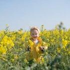 Ragazzo in piedi nel campo di fiori gialli — Foto stock
