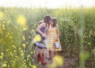 Two girls with buckets picking flowers — Stock Photo