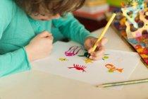 Junge sitzt an einem Tisch, Zeichnung — Stockfoto