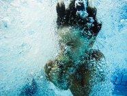 Мальчик Холдинг нос под водой — стоковое фото