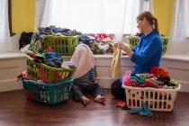 Mãe com filho rodeado de cestos para roupa suja — Fotografia de Stock
