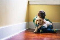 Junge umarmt Golden Retriever Welpen — Stockfoto
