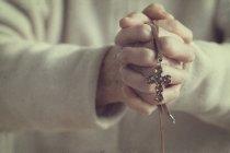 Woman holding crucifix — Stock Photo