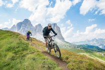 Man and woman on mountain bikes racing — Stock Photo