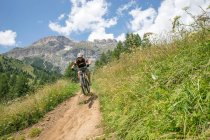 Uomo in sella alla sua mountain bike — Foto stock