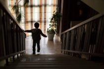 Boy walking down stairs — Stock Photo