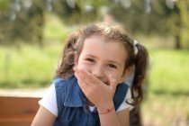 Girl holding hand in front of mouth — Stock Photo