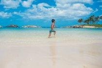 Boy running along beach — Stock Photo