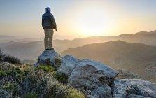 Человек, стоящий на вершине горы — стоковое фото