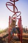 Junge schwingen auf Klettergerüst — Stockfoto