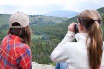 Femme et fille à la recherche par le biais de jumelles — Photo de stock
