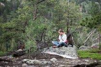 Mädchen sitzen im Wald Text-messaging — Stockfoto