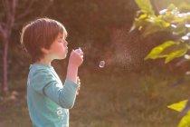 Menino soprando bolhas de sabão — Fotografia de Stock