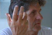 Hombre hablando y haciendo gestos con la mano - foto de stock