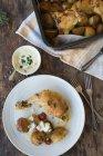 Gebratenes Huhn und Kartoffeln mit Sauce über Holztisch — Stockfoto