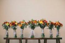 Belos buquês de noiva e damas de honra em bancos de madeira — Fotografia de Stock