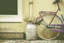 Велосипед прикутий біля будинку поруч із молочних відро з квітами — стокове фото