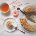Pane di banana con pezzo sul piatto e tazza di tè sulla tovaglia bianca con i fiori — Foto stock