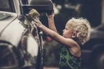 Vista laterale del ragazzino sveglio con capelli ricci, lavaggio auto — Foto stock