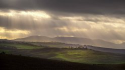 Sunlight streaming through clouds, Pienza, Tuscany, Italy — Stock Photo