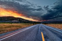 Scenic view of straight road at sunset under dramatic sky — Stockfoto
