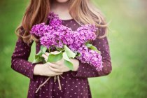 Cropped image of girl holding bunch of lilac flowers against blurred background — Stock Photo