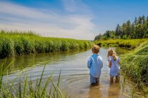 Rear view of brother and little sister standing in river at nature — Stock Photo