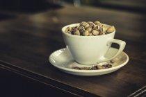 Nueces de pistacho en una taza blanca en platillo - foto de stock