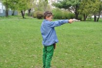Boy playing with a toy gun on lawn — Stock Photo