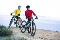 Two men leaning against mountain bikes in nature — Stockfoto