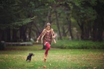 Girl chasing puppy dog in park — Stock Photo