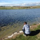 Boy crouching on riverside and looking at water — Stock Photo