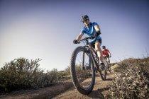 Two men mountain biking down track in nature — Stock Photo